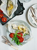 Seabass baked in parchment with roasted tomatoes with rocket