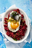 Labskaus (traditional dish from Northern Germany featuring salted meat, potatoes and onions) here made with corned beef with a fried egg and roll mop herring
