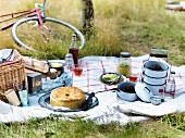 Picknick mit verschiedenen Gerichten auf weisser Tischdecke, im Hintergrund ein Fahrrad