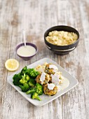 Salmon cakes with sweetcorn and spinach on a creamy lemon sauce served with broccoli and couscous