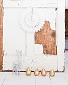 Gold and copper pear ornaments and white reindeer in front of shabby-chic wooden wall