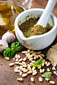 Pesto in mortar surrounded by ingredients