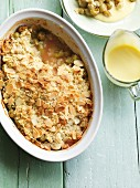 Gooseberry crumble in a baking dish with vanilla sauce