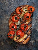 A slice of toasted bread topped with grilled tomatoes (seen from above)
