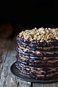 Armenian layer cake with coffee glaze, chopped walnuts and chocolate