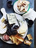 Käseplatte mit Crackern, getrockneten Trauben und Wein