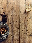 A bowl of nuts and a glass of wine on a wooden surface