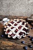 A blueberry tart with a lattice lid and icing sugar