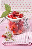 Strawberries and wild strawberries in preserving jar with sugar