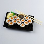 Maki sushi with salmon, soy sauce and ginger