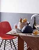 Eames Chair vor Holztisch mit Tellerstapel, Gerichten unter Cloches und Champagnerflasche