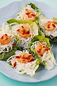 Mini glass noodle nests with spicy prawns on lettuce leaves