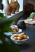 Madeleines und Gugelhupf auf Gebäckständern vor Fenstersims in Landhausküche