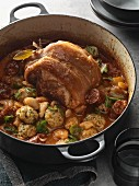Slow-roasted pork shoulder with butter beans and dumplings