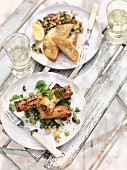 Filo pastry rolls on a pea salad, courgette and halloumi parcels with bulgur salad
