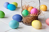Colourful Easter eggs in and next to a wire basket lined with straw