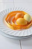 Yellow and orange Easter Eggs with a ribbon on a plate