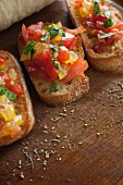 Bruschetta topped with basil and seasonings on a wooden surface