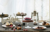 Cupcakes, pralines and berry cake with vintage scales on an old wooden table in front of a window