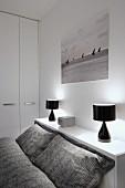 Graue, gemusterte Bettwäsche auf Bett vor Ablage mit schwarzen Tischleuchten, darüber Schwarzweiss-Photo mit Segelbooten