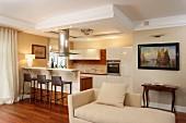 Helle Recamiere in klassischem Stil, im Hintergrund moderner Kochbereich mit Barhockern vor Theke in traditionellem Wohnraum