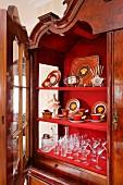 Antikes Geschirr imJugendstil und Gläser auf roten Ablagen in offenem Vitrinenschrank im Barockstil