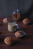 Homemade cinnamon muffins, a cafe latte and cinnamon sticks