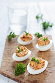 Devilled eggs with dried tomatoes and fresh parsley on a wooden board