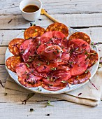 Watermelon carpaccio with sausage and ham