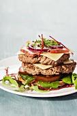Offener Doppel-Hamburger mit Schinken, Käse, schwarzen Tomaten, roten Zwiebeln und Kresse