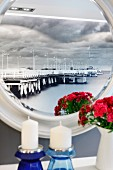 Historische Landungsbrücke auf einer Fototapete als Reflektion in einem runden Spiegel; Kerzen und Blumenstrauss im Vordergrund