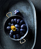 Fresh plums in a metal bowl (seen from above)