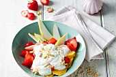 Colourful fruit quark with chopped almonds and pine nuts