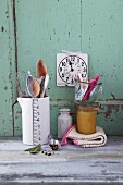 An arrangement of kitchen utensils for stirring, a clock and a preserving jar