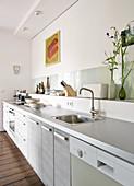 Moderne Küchenzeile mit hellgrauer Arbeitsplatte, Ablage vor Wand mit Küchenutensilien