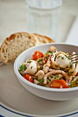 Squid salad with tomatoes, olive oil and herbs