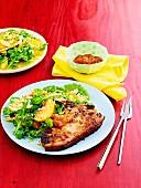 Mariniertes Schweinekotelett mit Pfirsichen, Orangenmarmelade und Salatbeilage