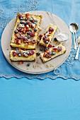 Bakewell Cheesecake mit Beeren, Mandelblättchen und Puderzucker