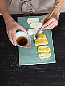 Halloumi being brushed with flavoured oil