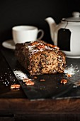 Banana, chocolate and pecan nut bread in front of a teapot and a tea cup