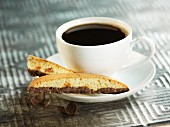 Almond biscotti with chocolate next to a cup of coffee
