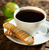 Biscotti with a lime glaze next to a cup of coffee
