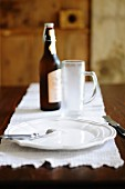 A place setting with a beer glass and bottle of beer