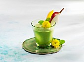A mango and spinach smoothie garnished with flowers