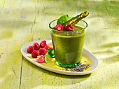 A spinach and banana smoothie with raspberries, chia seeds and acai powder