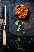 Ossobuco milanese with fresh parsley on a black table