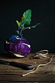 Purple kohlrabi with a knife and twine on a wooden table