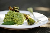 Pea and mint purée with fried artichokes on a white plate with a fork