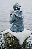 Frau mit Teetasse im Schnee am Seeufer