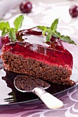 A slice of chocolate cake with cherries and jelly